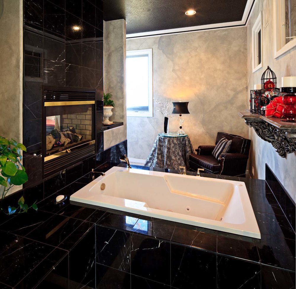 After- New tub on other side of sitting area (through the fireplace) with black marble and tub decking.
