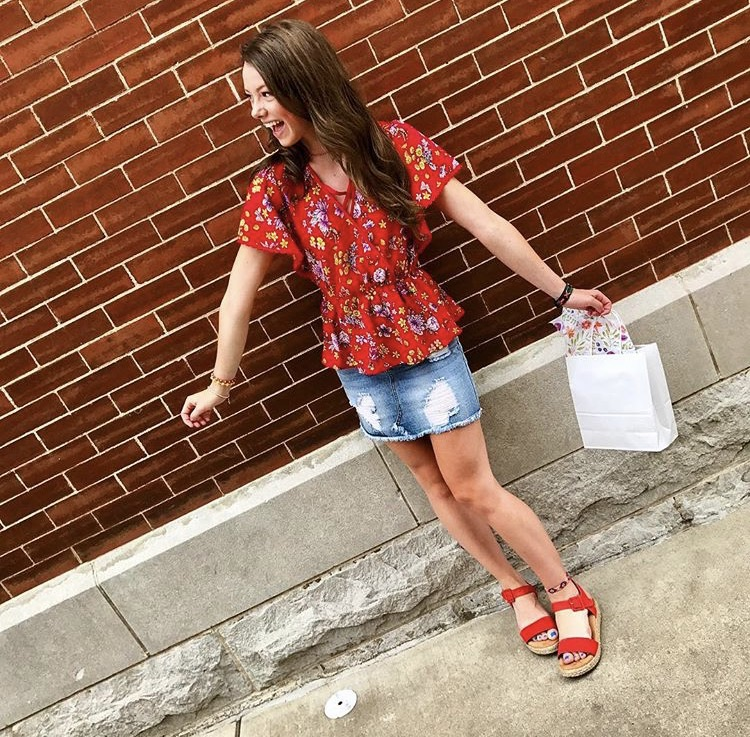 MARSHALLS SHIRT  has a cinched waist, with a 70s floral print and crisscrosses at the chest   DENIM SKIRT  from a local boutique, Logo N Stitch   RED PLATFORMS  are from designer Kenneth Cole at Dillard's