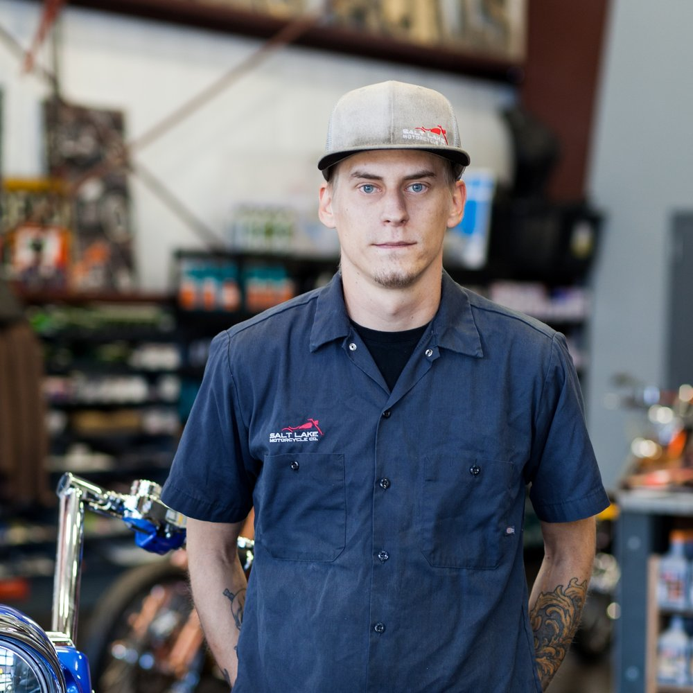 Tom russell - Tom Russell is Salt Lake Motorcycle Co.'s Lead Service Technician. As a Salt Lake City native, Tom loves the local business environment of Salt Lake Moto and is the proud owner of four motorcycles.His favorite part about his job—and working with motorcycles in general—is that he gets to use his brain while working with his hands. Tom joined the Salt Lake Moto team after closing his own shop. He heard Chris needed a tech, came in to apply and the rest is history.Tom's motorcycles: 1973 Honda CB360, 1981 Honda XR200R, 2006 KLX, 2005 Harley Sportster.
