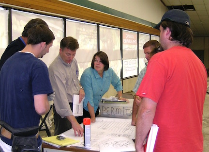 Tyler Myers, Myers Group President, and Christine Hurley, Executive Director of Goosefoot in 2009, go over blueprints for the store's renovation.