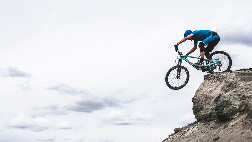 Mountain Biker dropping off moonlike cliff.jpg