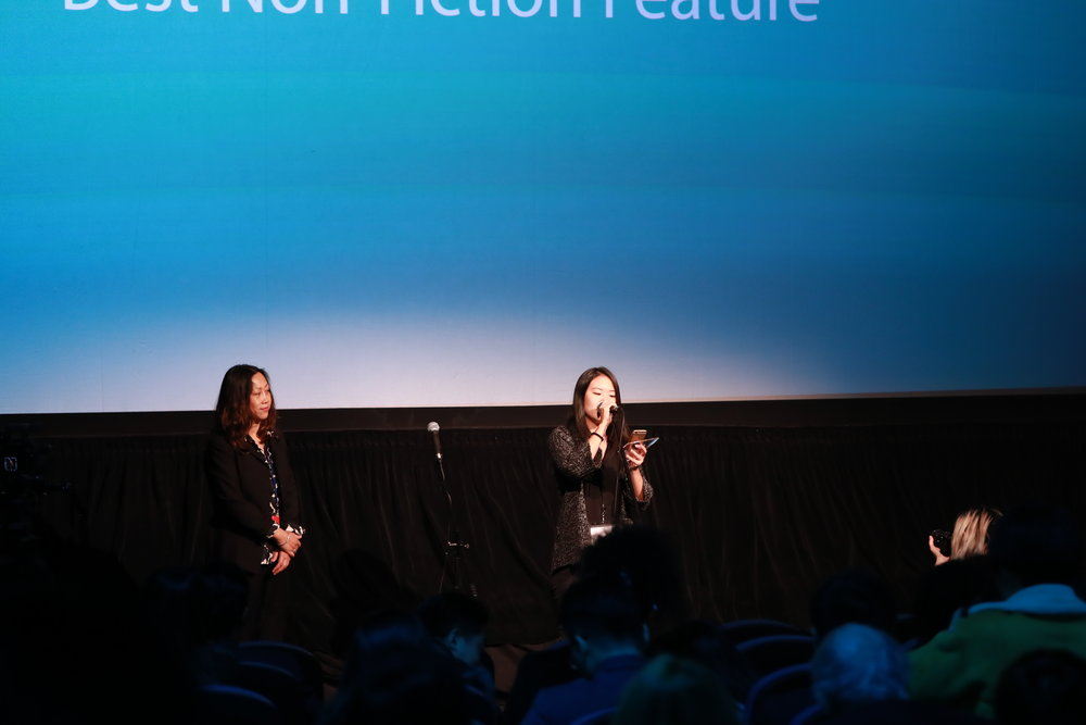 Jury Zhen Zhang presents the Best Non-Fiction Feature Award (left) programmer Rena Wang reads message from Tianqi Yu, co-director of  China's van Goghs  (right)