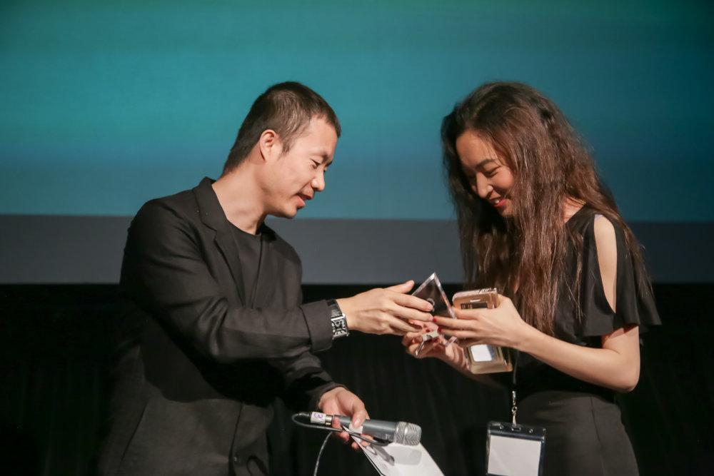 评委会成员李睿珺(左)向《柔情史》的导演代表颁发最佳剧情长片奖。