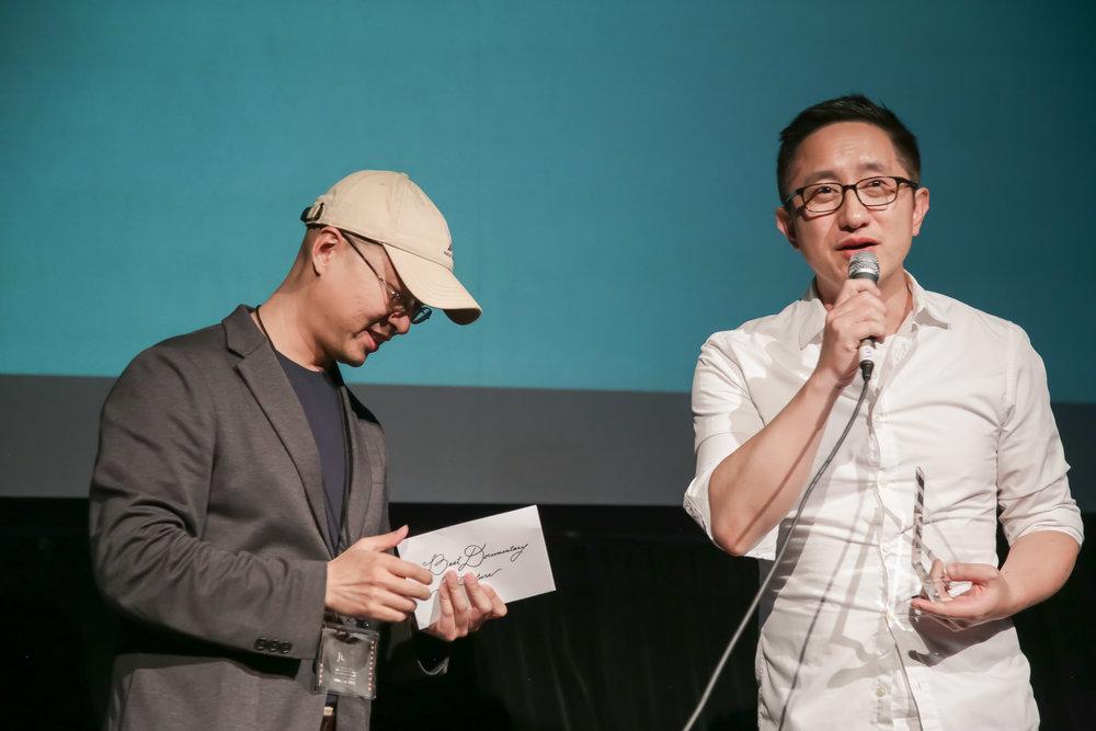 评委会成员梁为超(左) 颁发最佳纪录长片给《虚你人生》的导演吴皓(右)。