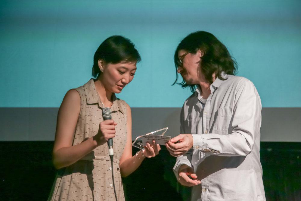 Jury member Helder Sun (right) presents the Best Experimental/Animation Short Award to Director Anchi Shen (left).