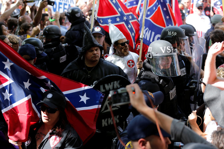 On Saturday, riot police in Charlottesville, Va., protected members of the Ku Klux Klan from counterprotesters as they rallied to oppose a proposal to remove a statue of Robert E. Lee from a city park.CreditJonathan Ernst/Reuters