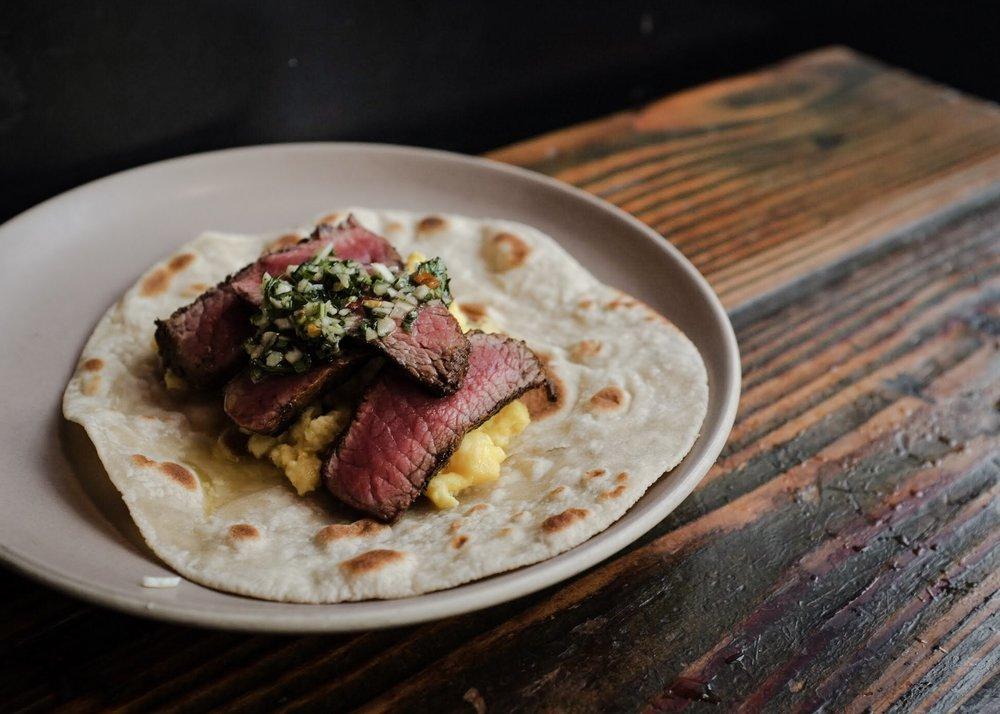 The Steak & Egg Breakfast Taco garnished with house=made chimichurri.