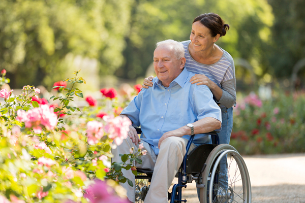 Senior-man-sitting-on-a-wheelchair-with-caregiver-000075015777_Full.jpg