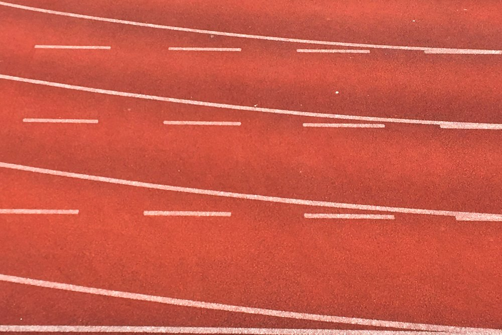 Photo of red track with white lines by Henry & Co. on Unsplash