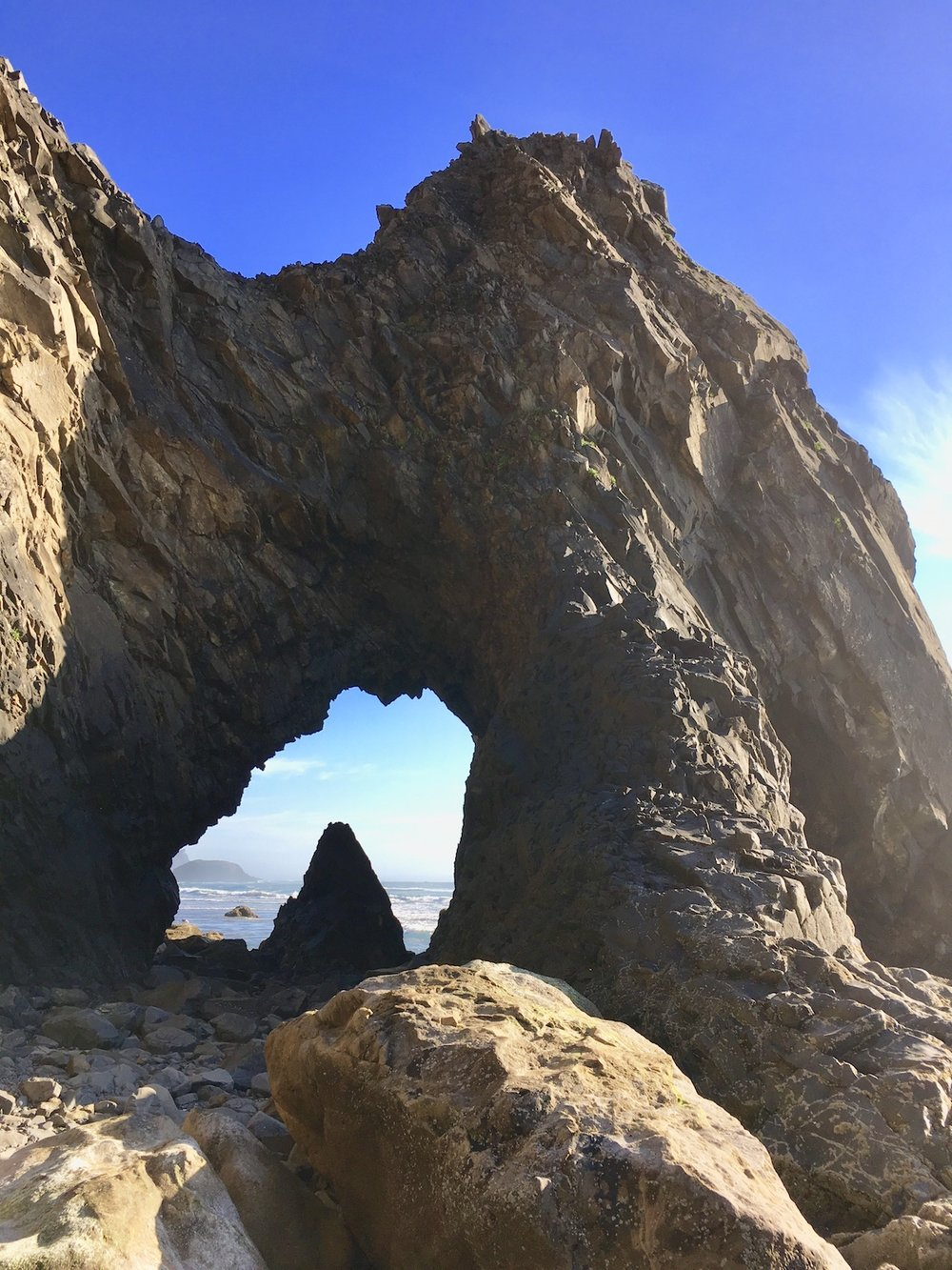 The Arch Cape arch sits just past the Arch Cape headland at the south of town