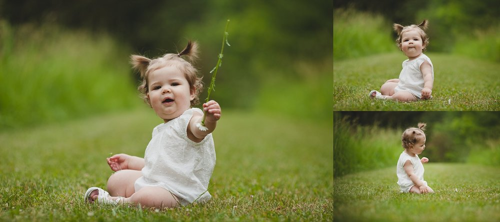 Sweet happy baby girl smiling and playing in the grass.