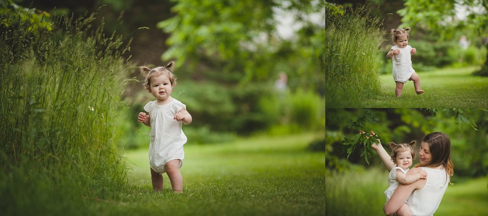 Baby girl dressed in white romper walking in the grass.