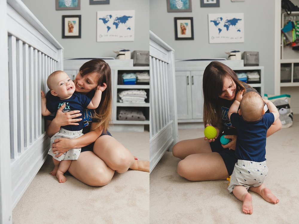 A baby boy with his mom in his grey, white and blue nursery.