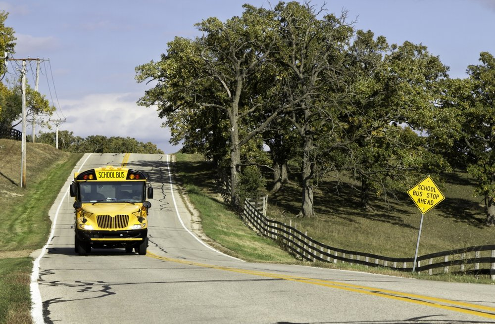 Yellow school bus driving on rural, tree-lined road