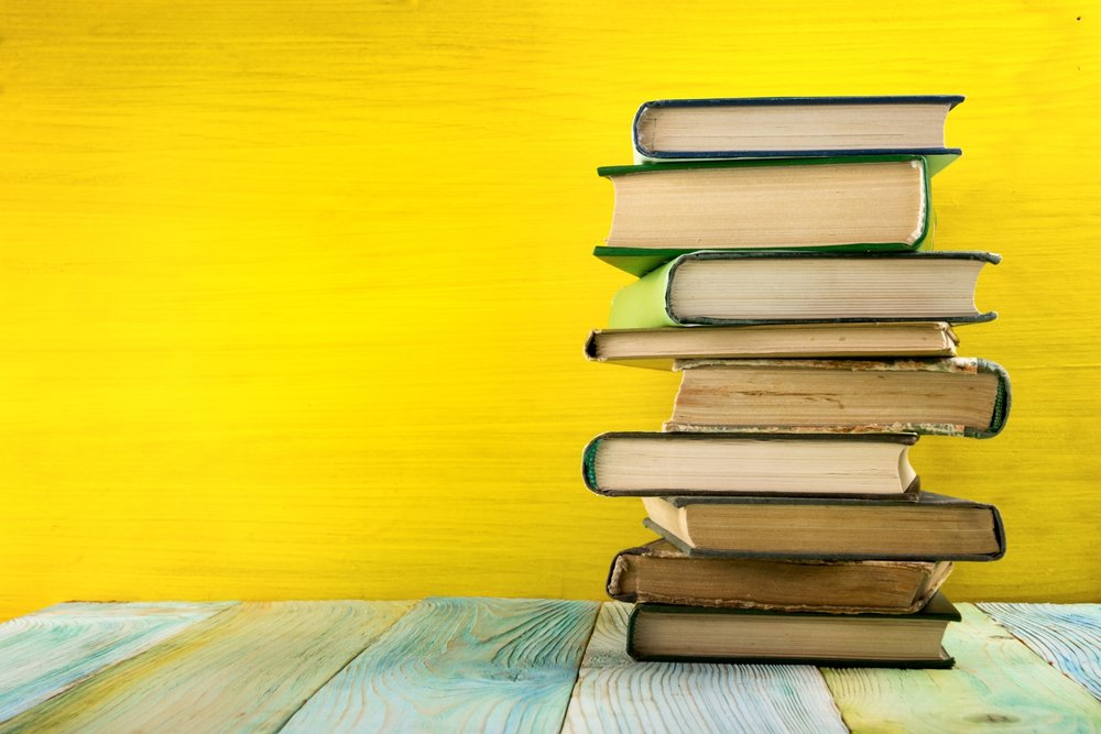 Stack of books, pages facing out on green table against yellow wall. Photo by Vimvertigo/iStock /Getty Images