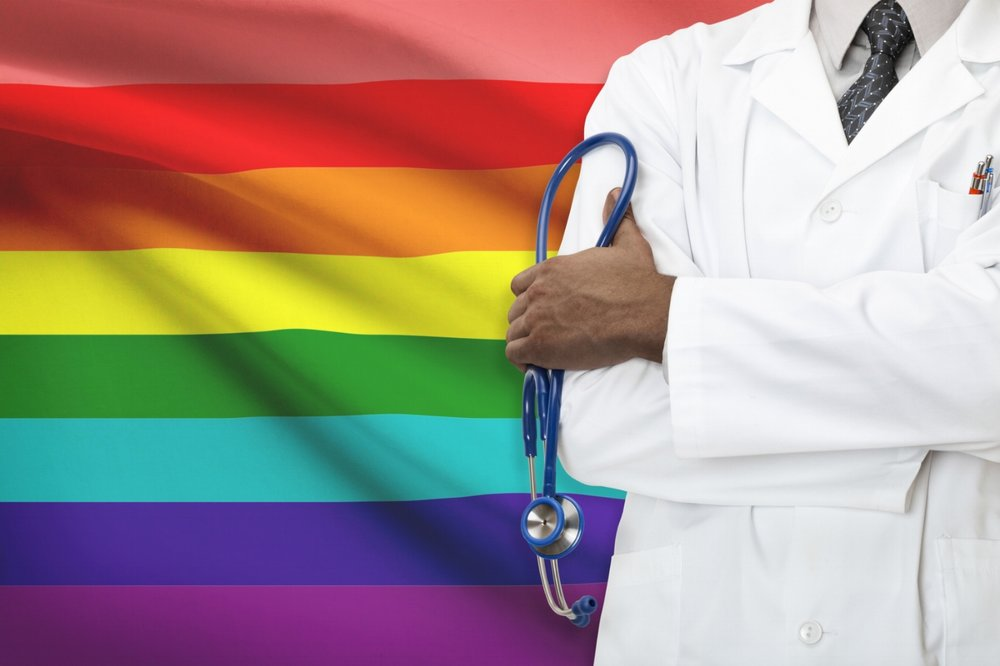 Medical professional (from the shoulders down) with stethoscope standing in hand arms crossed standing against a Pride flag.