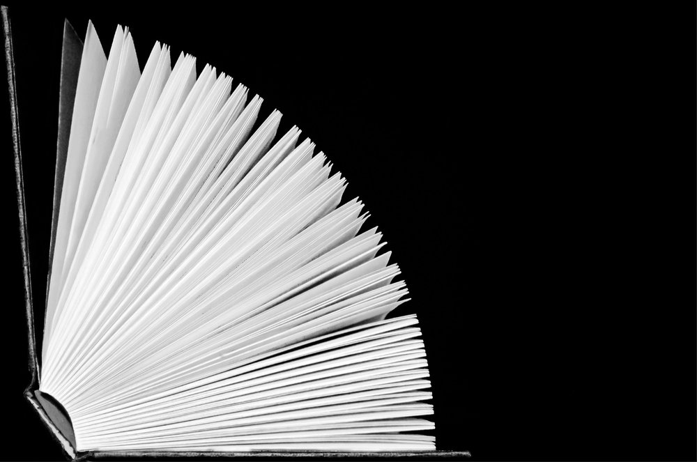 Black background with hardback book with white pages fanned open