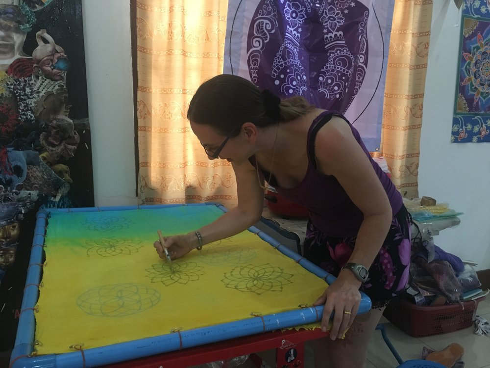 Inanna has an adjustable PVC frame she uses to stretch fabric she uses in her batiks. Here she uses hot wax to create a resistance pattern. The background color will show through when she washes out the wax.
