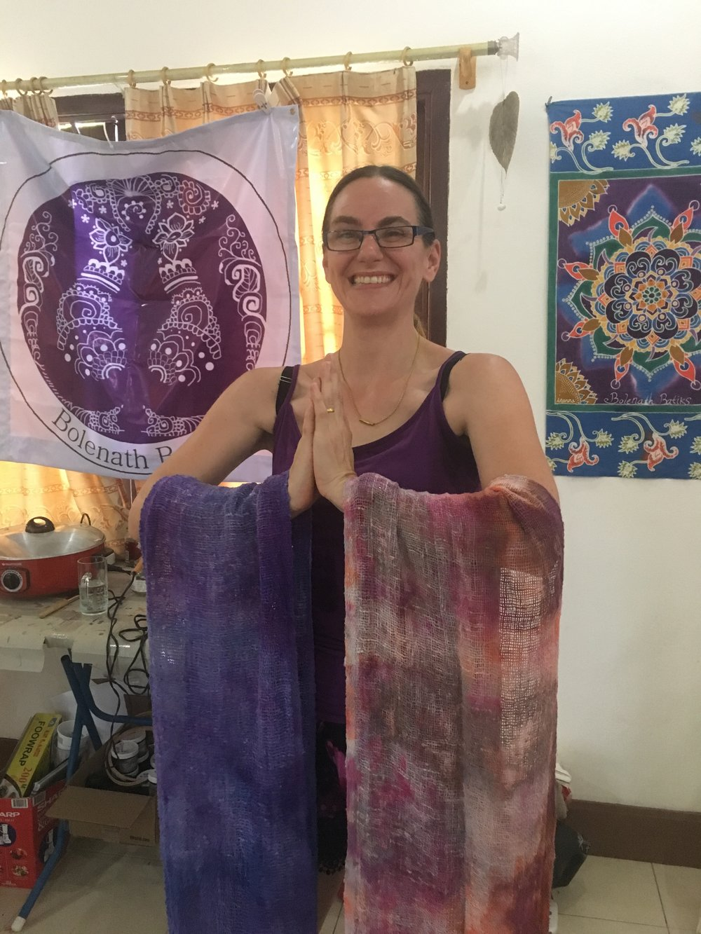 Innana poses with some scarves she's dyed. In the background is the logo for her company Bolenath Batiks and a batik she made in Bali.