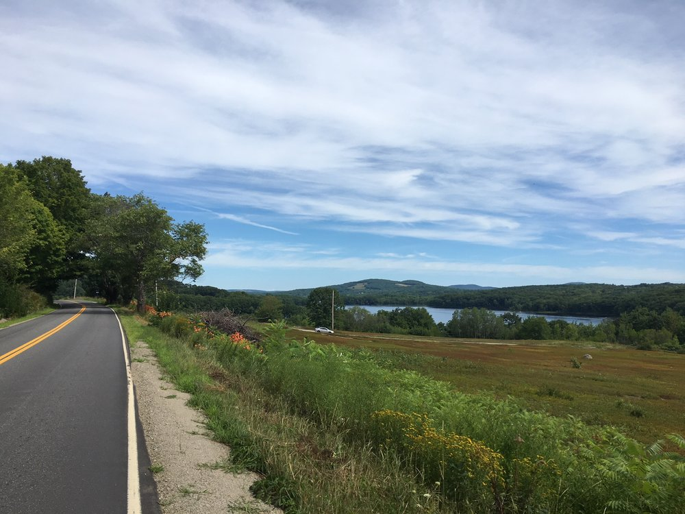 I've ridden on a lot of country roads with no shoulders. Note the lake and mountains in the background. Maine is so beautiful.