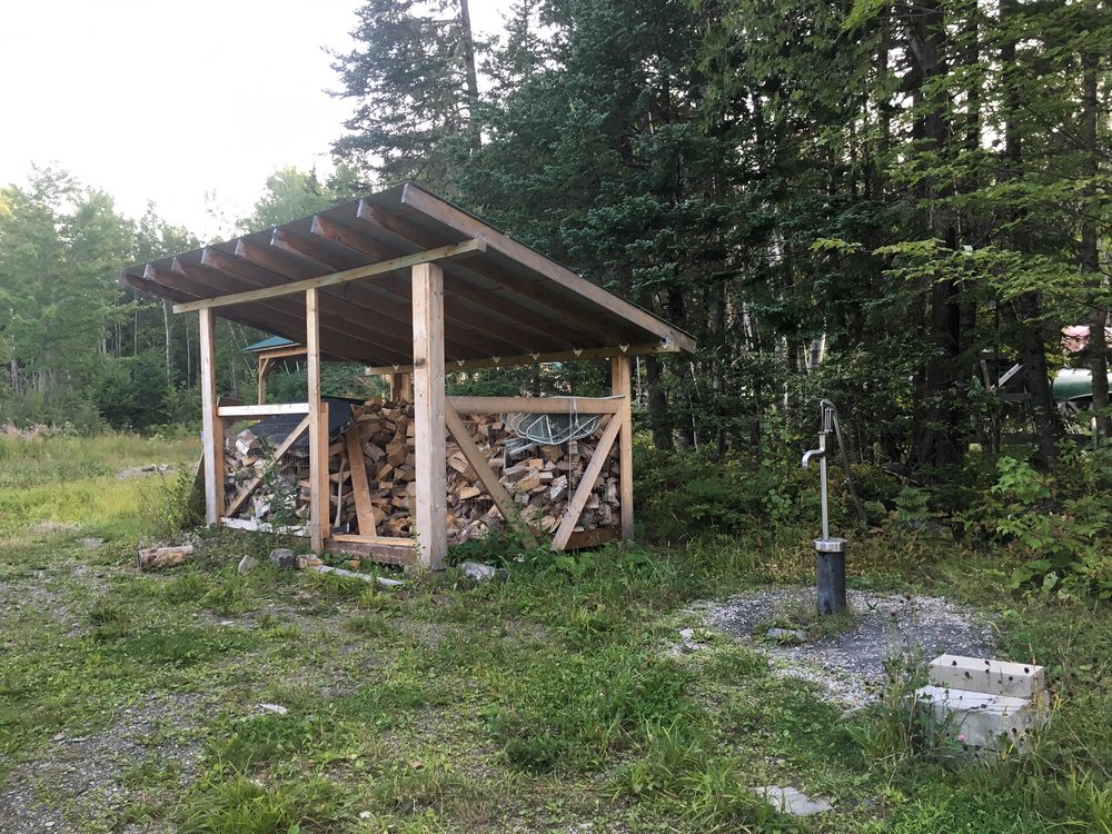 "The woodshed and one of the two wells on the Jack Mountain Bushcraft School Property. The ""Pavillion"" is a two sided structure in the background where we sometimes have class."