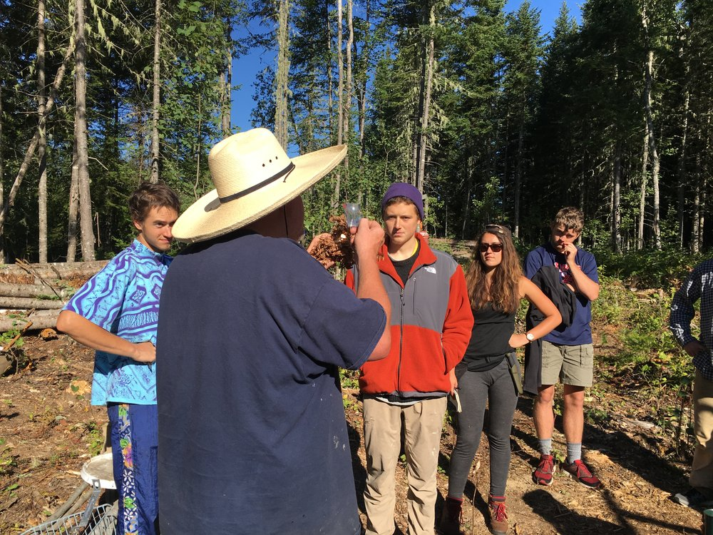 Sam, far right, watches bushcraft instructor Tim demonstrate how to ignite a tinder bundle with a magnifying lens.