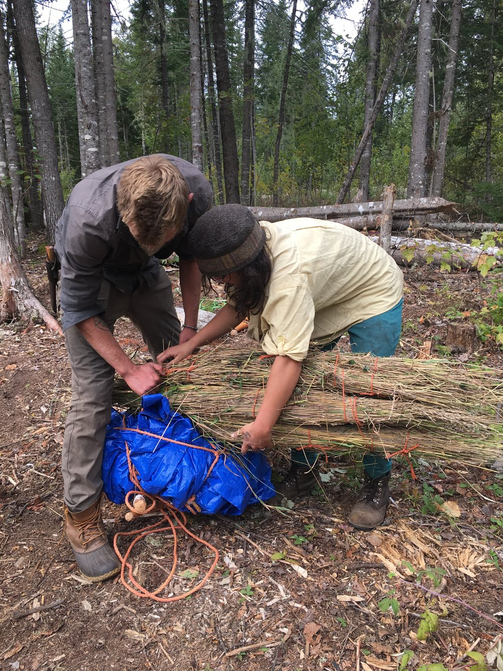 Molly ties a grass mat to her pack frame with the assistance of instructor Chris.