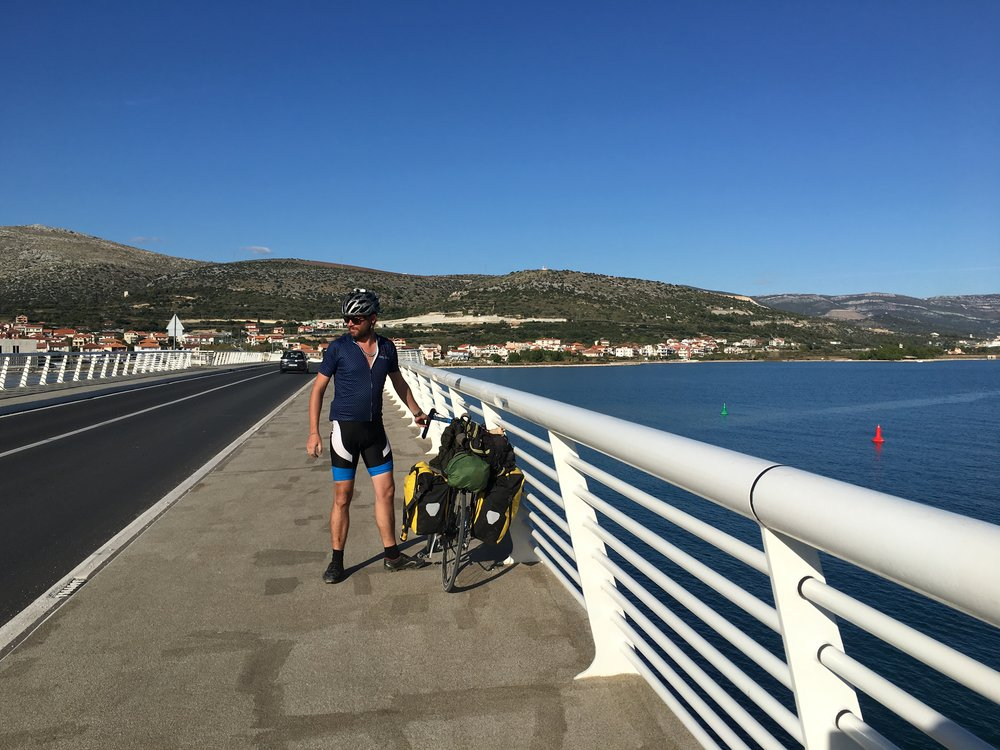 Craig stopped on the bridge back to the mainland to help a fellow cyclist with a flat.