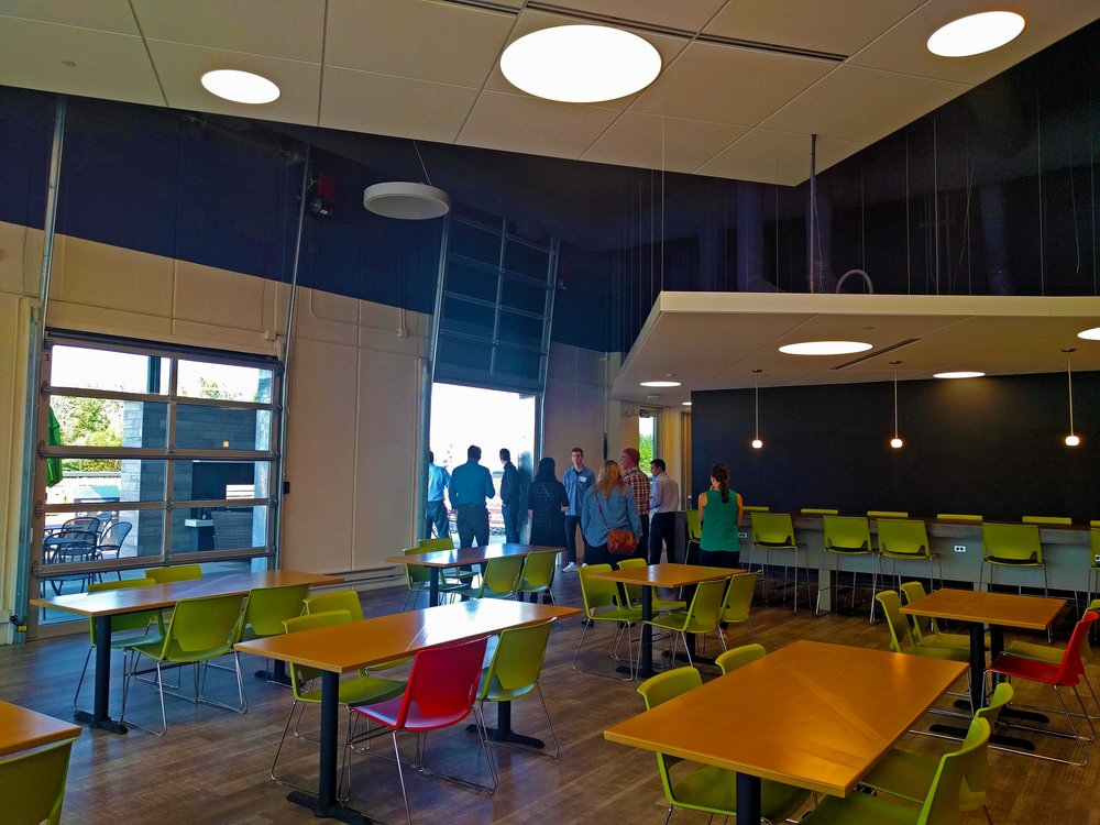 Their cafeteria doubles as a meeting area and as a more relaxed area for employees to work. The space spills out onto the outdoor patio and fireplace through large overhead doors.