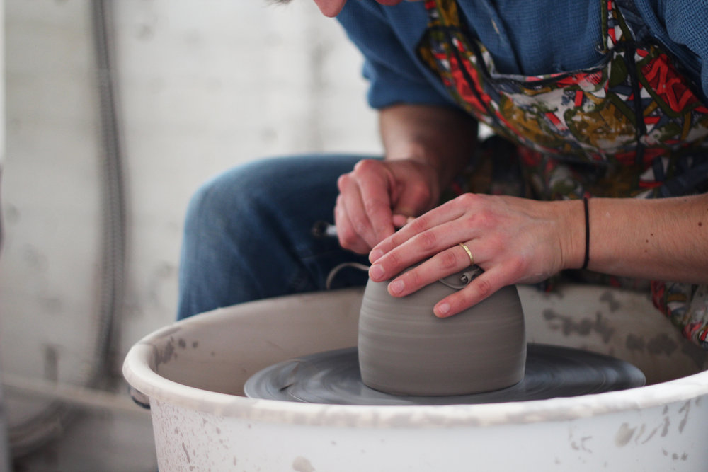 All of our wheel-thrown pieces  are allowed to dry for about a day and then are put back on the wheel to trim– in this photo Alicia is trimming the bottom of a large three-legged planter.
