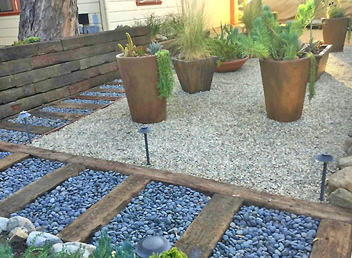 unique walkway_black stones w railroad ties_fence_gravel bed w large pots.jpg