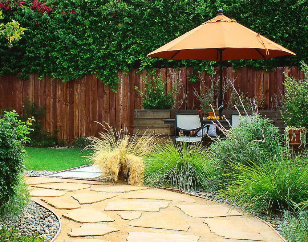 A Backyard Landscape made for Enjoyment and Relaxation. It includes Drought-tolerant Plants, a Flagstone & Decomposed Granite Walkway, a Concrete Paver Patio with River Rocks, a Wood Planter Box and a Lawn Area.