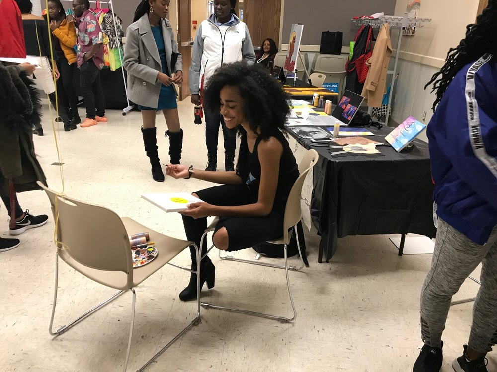 Misha Bucknor, sophomore kinesiology major, not only brought her paintings, but did a live painting session at the show. Photo by Amina Lampkin.