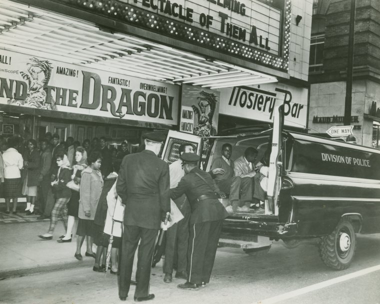"Schomburg Center for Research in Black Culture, Photographs and Prints Division, The New York Public Library. ""CORE demonstrators being arrested outside segregated movie theater showing ""Goliath and the Dragon,"" at unidentified location, ca. 1960"" The New York Public Library Digital Collections. 1960.  http://digitalcollections.nypl.org/items/83d56b71-44fb-2a82-e040-e00a1806337f    The Congress of Racial Equality demonstrators are being arrested in the above photo. CORE is a Civil Rights organization that worked to create equality in America.  This particular demonstration was in front of a movie theater in 1960."