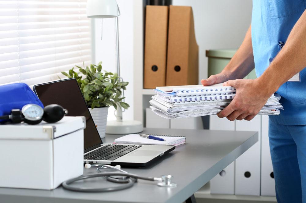 Médecin déposant une pile de dossiers sur une table sur laquelle se trouvent un stéthoscope et un ordinateur.