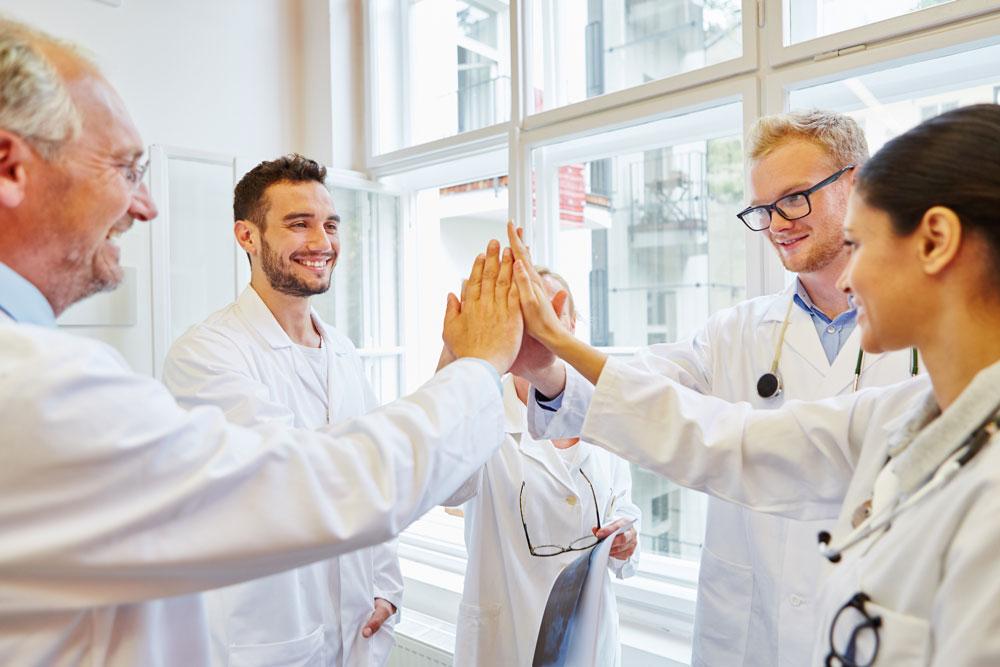 """Groupe de médecins heureux faisant un """"Top-là""""."""