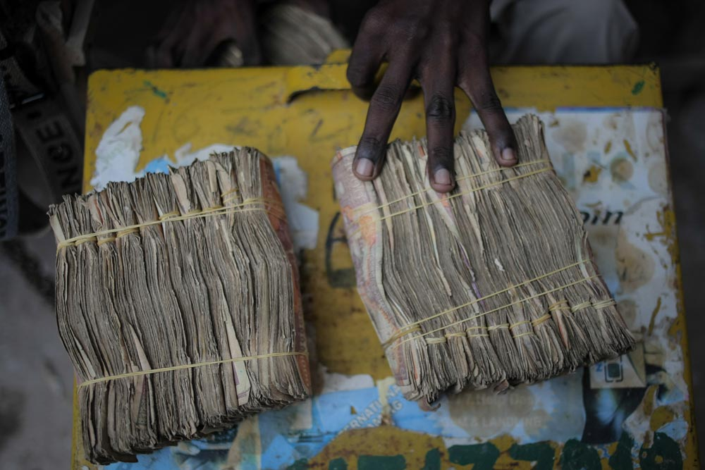 A money exchanger displays Somali shilling notes on the streets of Mogadishu. Credit: UN Photo/S. Price.