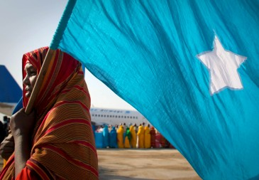 A woman carries the Somali flag during a cememony at Mogadishu International Airport. Credit: UN Photo/S. Price