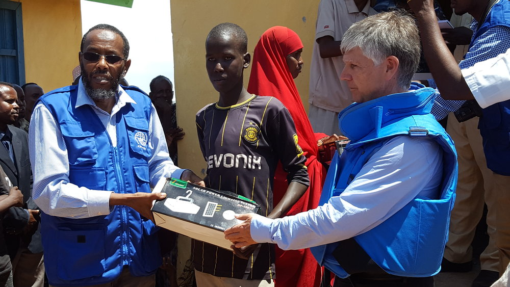 Special Advisor Walter Kaelin (right) hands over solar equipment to field staff in Kismayo for distribution to displaced persons in the camp. Credit: UN Photo