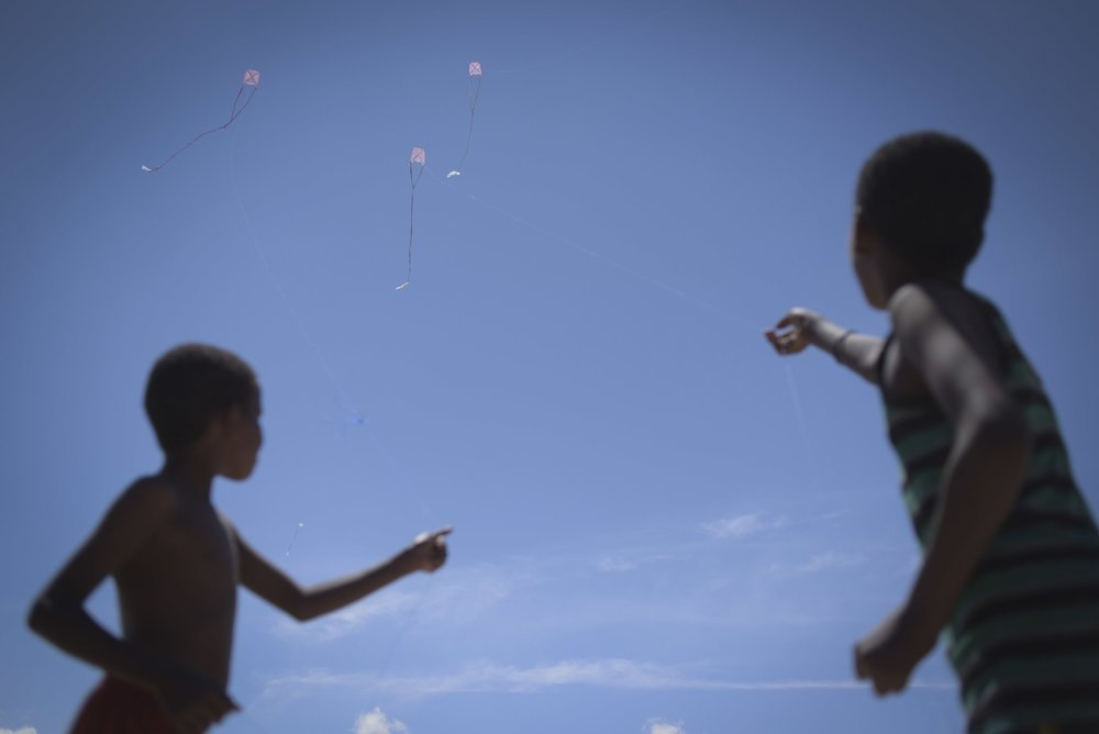 Two boys fly their kites in the coastal city of Bosasso. Credits: UN Photo/T. Jones