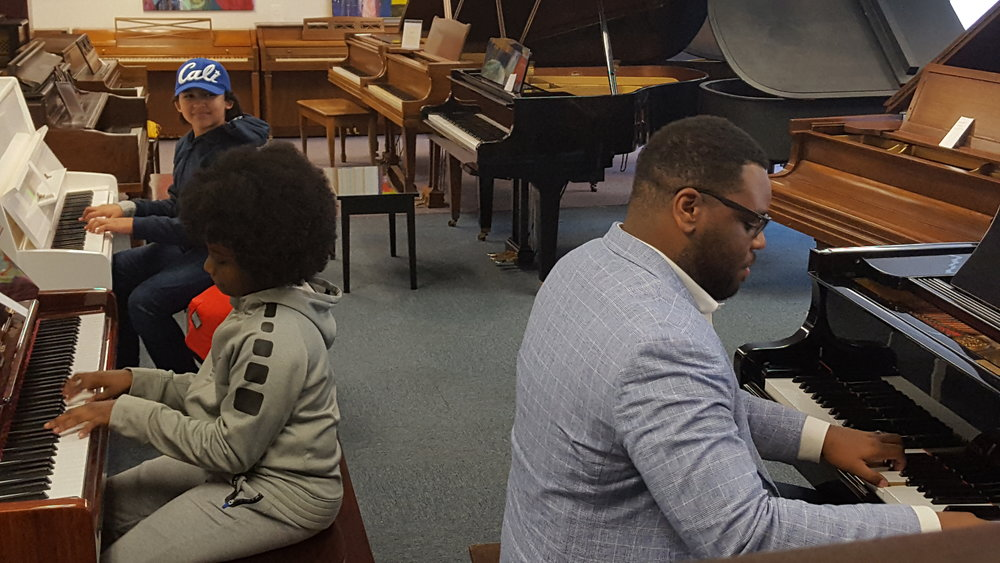 Faculty artist Rufus Ferguson jams with our Jazz Orchestra pianist and his Jazz Academy student.
