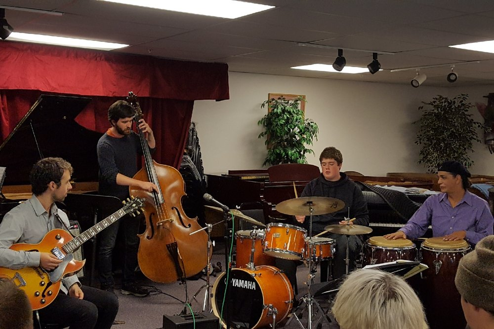 Faculty artists Nathan Borton, Andrew Peck, and Kevin Jones work with a Jazz Academy student on drums during a jam session.