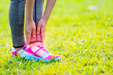 75711317_S_foot_pain_girl_sneakers_leg_hand_gripping_grass.jpg