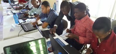 Alia, in dark suit, training Haitians on using the model. Photo provided by Didier Alia.