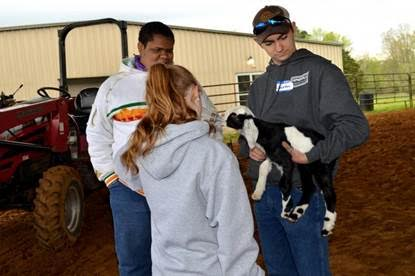 Briley Mitchell, back to camera, feeds a baby goat held by Jonathon Sink, right. DeKavion Jones looks on. Photo by Katie Pratt, UK agricultural communications