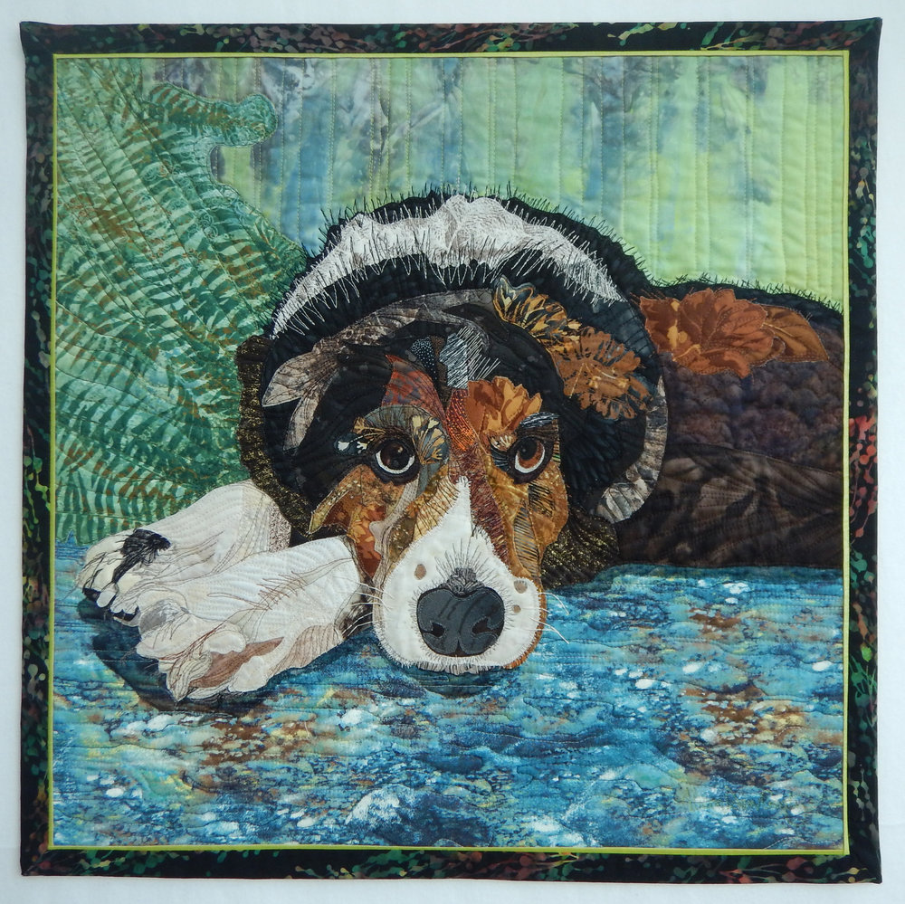 """Leo - 23"""" x 23""""Accepted into the Canadian Quilters' Association National Juried Show 2016With much meaning and gratitude this portrait was brought to life. A physician and friend was intrigued with my previous work using fabric as an art medium and she asked me to make a portrait of her Border Collie, Leo. He is a beloved family pet who is in his twilight years. It was my goal to communicate his loyal and gentle spirit in fabric. For me it comes alive when I get the eyes right!"""