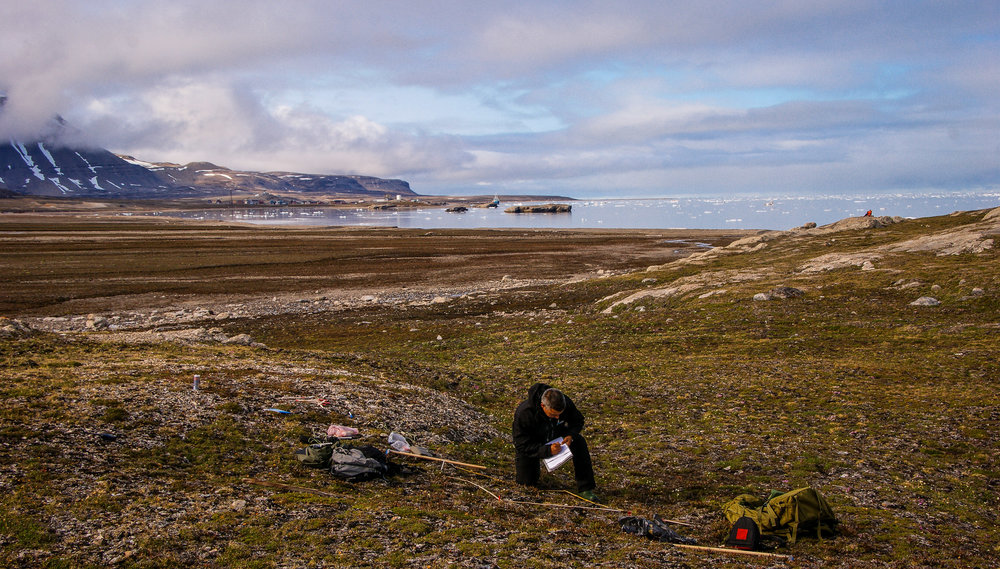 Senior researcher in ecology Jarle W. Bjerke is doing fieldwork on Svalbard. Kongsfjorden and Ny Ålesund in the background.  JONAA©Trond Johnsen