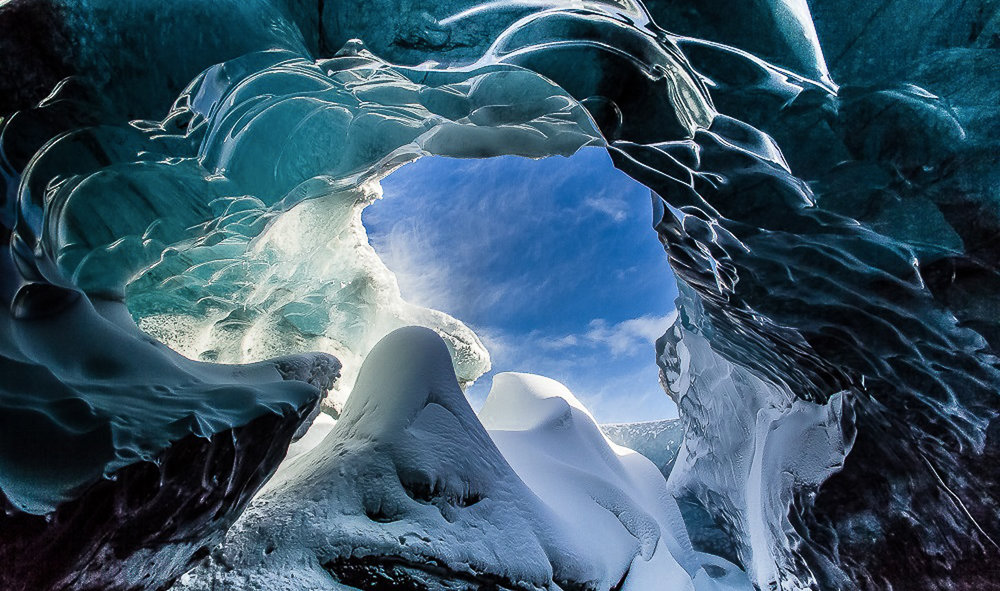 The colours inside an ice-cave differ due to the daylight and sunlight outside that gets in through holes and cracks in the ice.  JONAA©Agust Runarsson