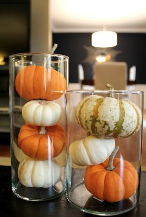 Easy Centerpiece Ideas - A quick and easy Fall centerpiece is a cinch to pull together. Just stop by your local craft store and pick up a few glass hurricane vases of different sizes, then fill with mini pumpkins, pine cones, acorns or your favorite Fall-inspired filling and viola!