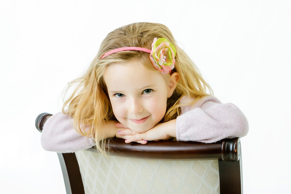 Portrait of young girl in the studio resting on back of chair